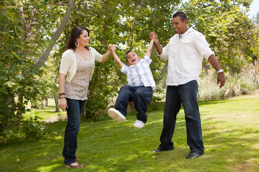 child swinging in arms of parents